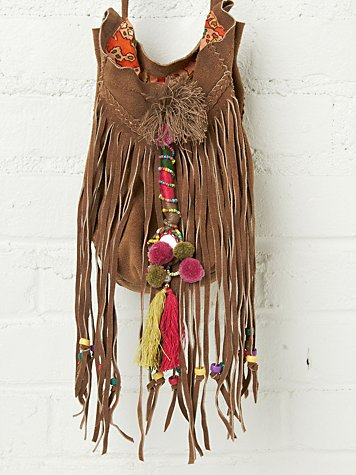 Suede crossbody fringe bag with colorful embroidered detailing, beads, tassels, and pompoms. Braided suede trimming across front