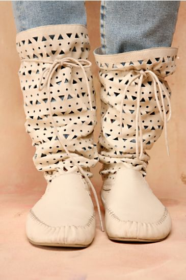 Moccasin style slouch boot with cutout detail and lace up back. Textured rubber sole.