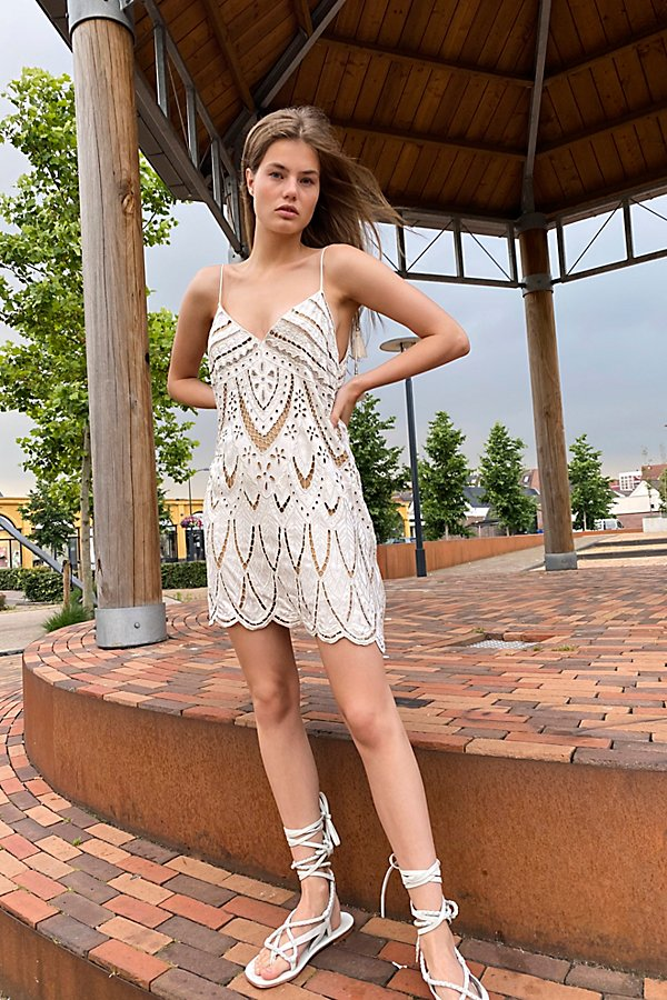 Shapeless mini dress featuring cutwork detailing. * V-neckline* Adjustable tie straps with tassel ends* Scalloped hem* Back zip closure* Lined* Fit note:* This style may run large, we suggest sizing down.